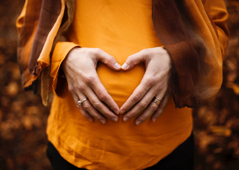 Pregnant woman with warm orange coloured clothes and background. She has her hands on the belly with a heart shape.