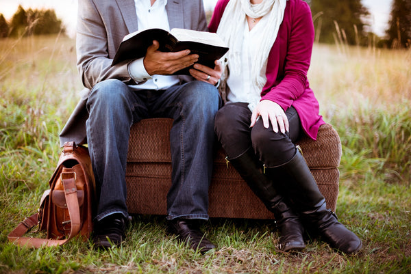 Two people sitting on a brown couch on the lawn and reading a book together