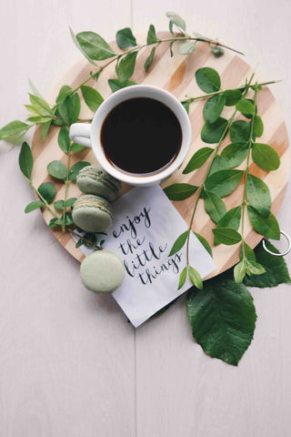 "A cup of coffee and some green leaves with a card writing ""enjoy the little things"""