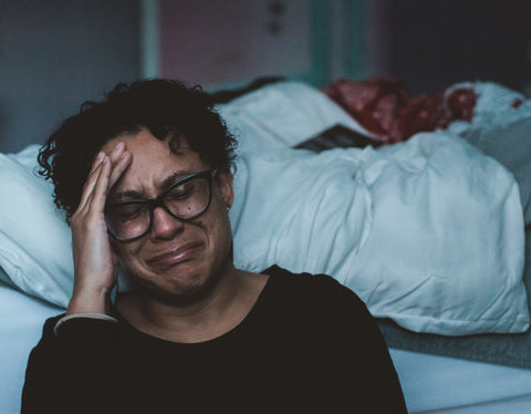 Woman in black sitting on the floor leaning against the bed crying