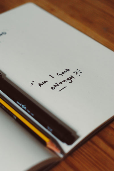 "A notebook with handwritten ""Am I good enough?"""