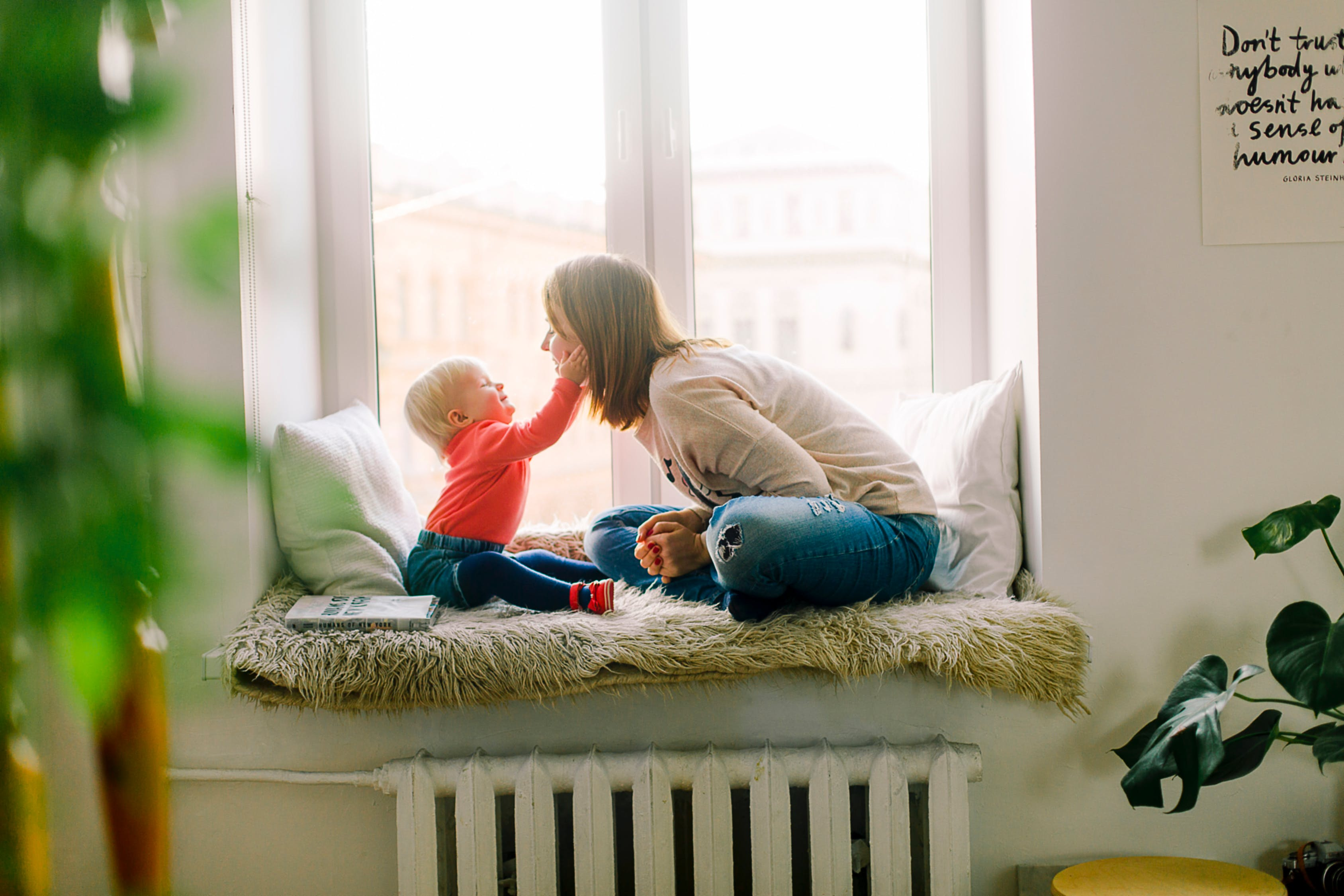 A mom is playing with her baby by sitting on the window to create special memories
