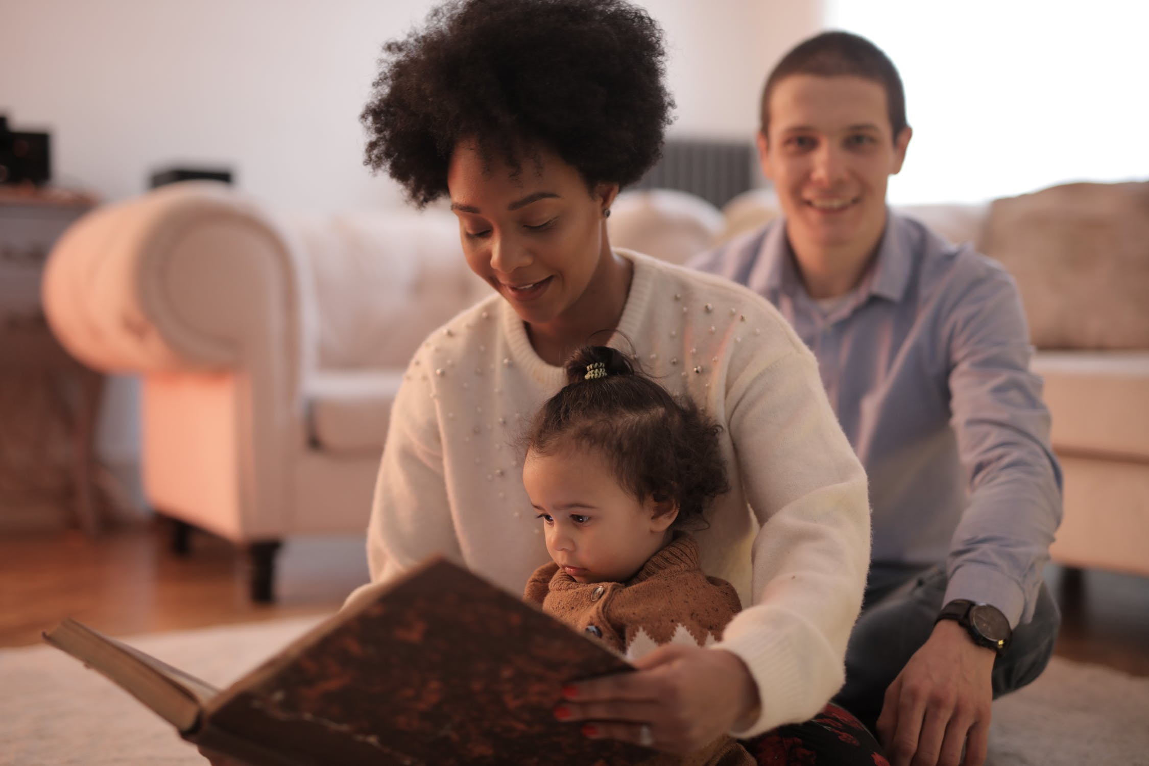 A happy family where parents holding a journal to share the baby bump stories to their baby child.