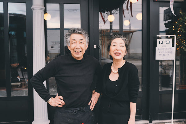 An old couple in classic black outfit smiling to the camera with confidence and grace