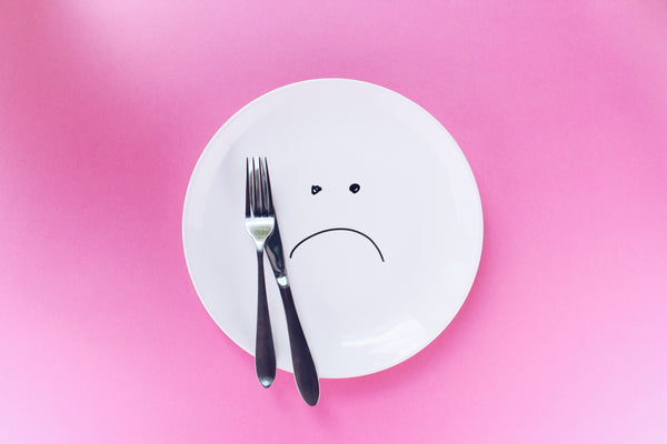White plate with fork and knife on the pink background. A sad smiley on the plate. Eating disorder, pregnancy cravings due to emotional hunger instead of physical hunger. Eating not due to joy