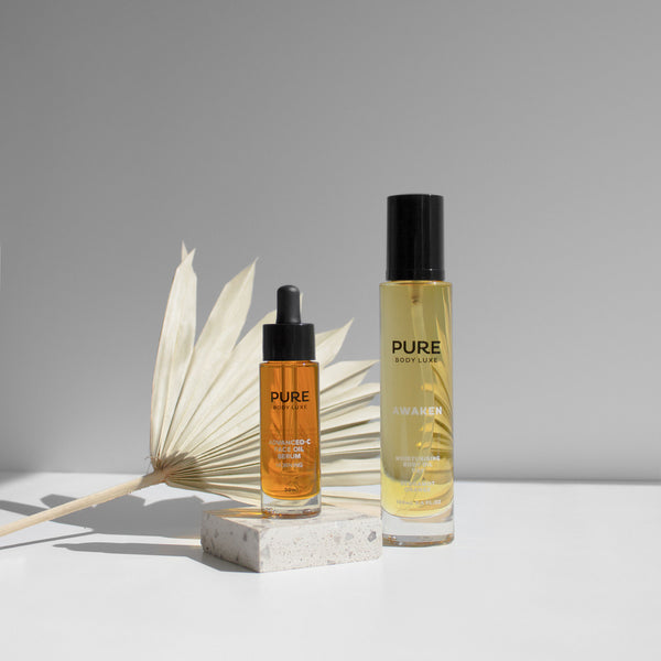 Advanced-C Face Oil Serum with Awaken 100ml Body Oil bottle with a decorative dried palm on the background