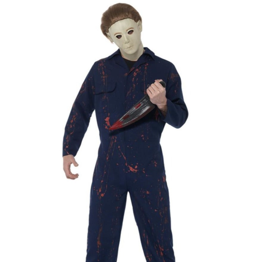 Blue fabric boiler suit. Plastic knife, black handle, silver blade with blood stains. Overhead rubber mask with openings for eyes, white with brown hair and eyebrows.