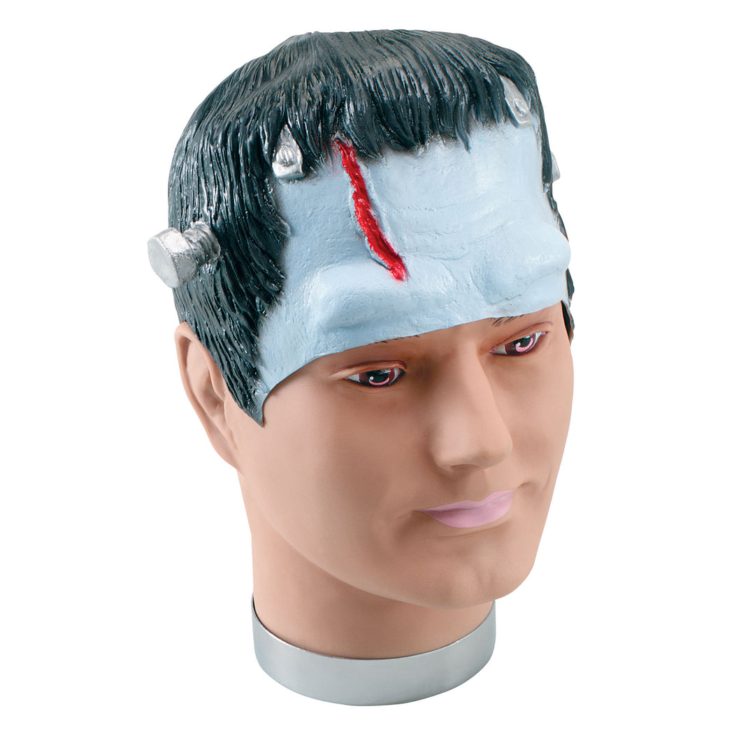Made of rubber this covers your head and forehead. It has black hair and bolts at either side with a red cut down the front.