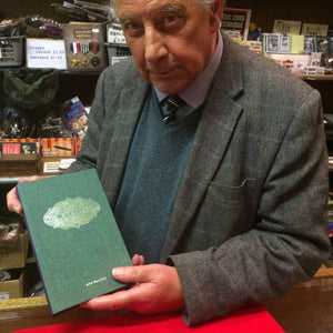 Roy Walton behind the counter in Tam Shepherds Trick Shop, holding a copy of his book 'The Complete Walton: Volume 3'.
