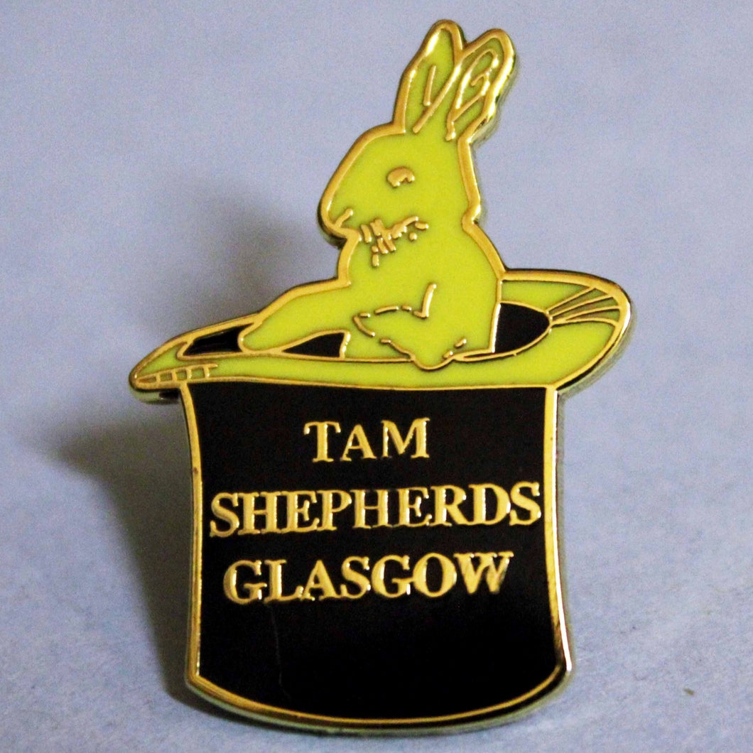 Black and yellow enamel shop logo (rabbit in a top hat) pin badge with raised gold lettering reads 'tam shepherds glasgow'. 21mm width by 30mm height