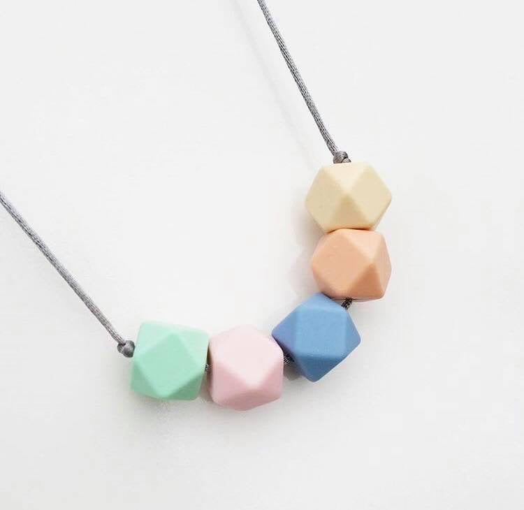 A silicone teething necklace in pretty summer pastel shades by Mama Knows at Our Kid