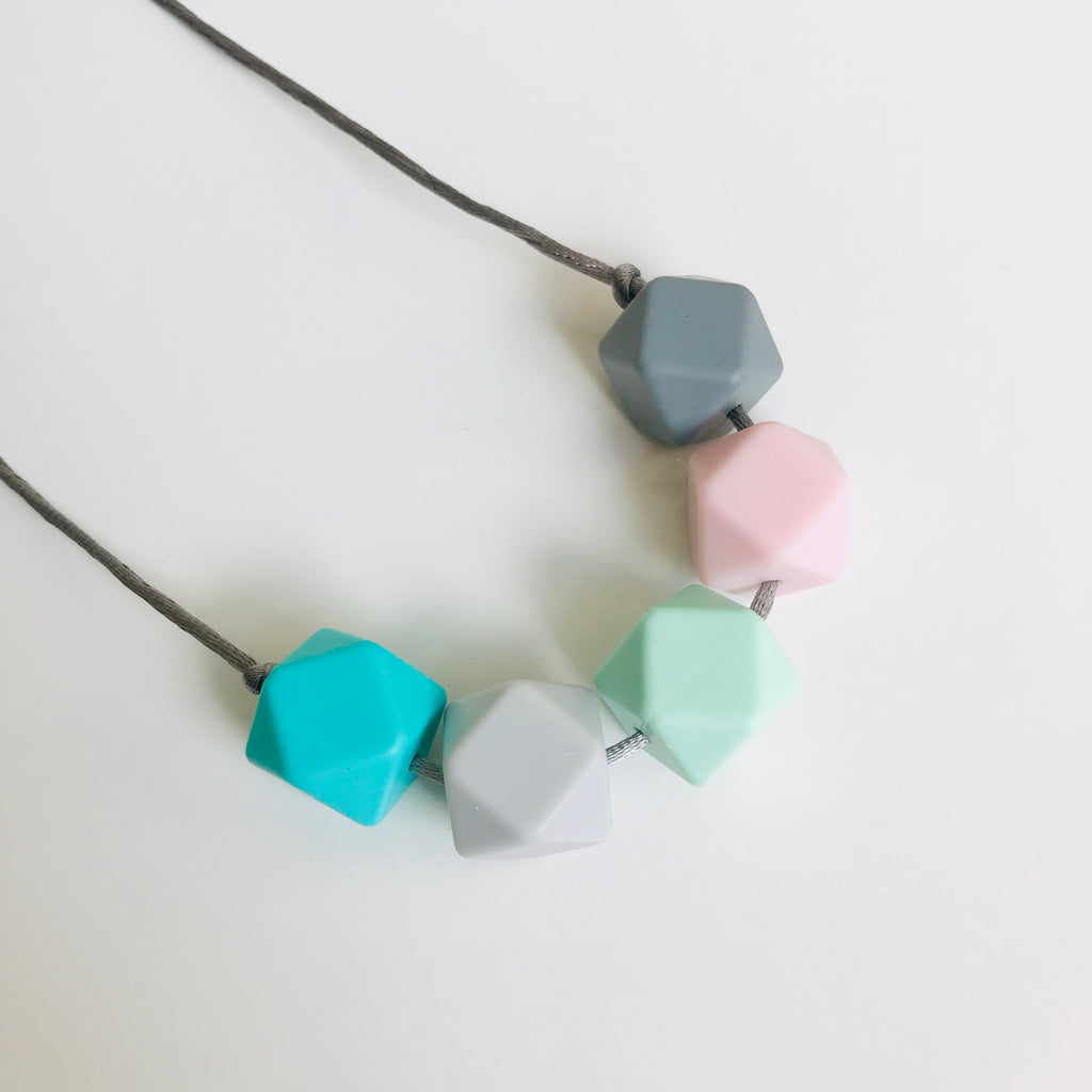 A silicone teething necklace in pretty pastel shades by Mama Knows at Our Kid