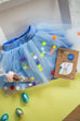 Image shows an Easter gift box for girls which includes a blue net tutu with pom poms a chocolate treat cone and Cotton twist craft kit.