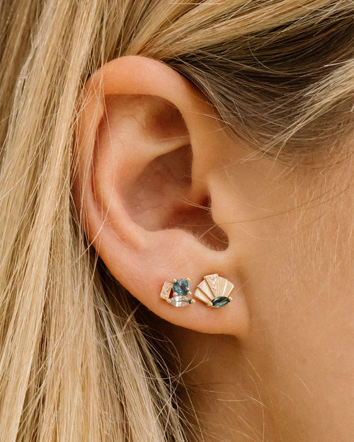 2 earrings on a girl's ear. To the left of the main earring hole is one 14k gold cluster earring that has a london blue topaz and white sapphire marquis. To the right of that is the 14k gold fan shaped earring with turquoise marquise.