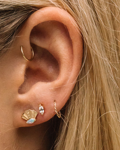 4 earrings on an ear. One is a gold fan design with an opal marquise. Next to it is a white sapphire marquise. To the right of it is a braided twist gold cuff earring. Above those 3 is a plain gold cuff.