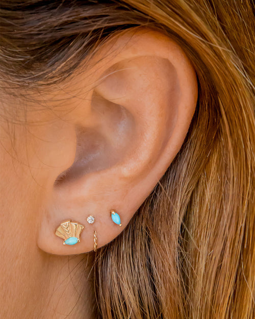 4 earrings on a girl's ear. Starting from the left is the 14k gold fan shaped earring with turquoise marquise. Next to that is white sapphire stud earring and braided twist gold cuff. On the very right of it is a turquoise marquise stud earring