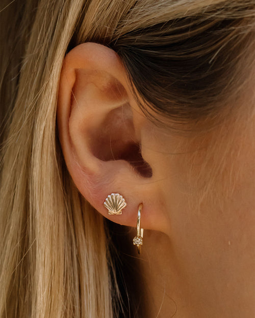 2 earrings on girl's ear. To the left of main earring hole is small shell stud earring. To the right is a u-hook shaped gold stud earring with one rhinestone detail.