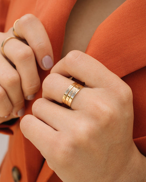 "girl wearing three rings on her left hand middle finger. 3 rings are stacked on her middle finger. The top ring has engraving ""queen"", below that has ""loved"", and after that has ""La Femme"""