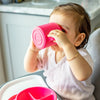 A cute little girl looking up and drinking out of her pink Learning Cup made from Silicone