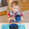 A young toddler holding in a big gulp in his cheeks while holding the navy Learning Cup made from Silicone
