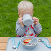 A little boy sitting at a table outside while drinking out of the gray Learning Cup made from Silicone