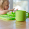A close up of the green Learning Cup made from Silicone with a little girl eating in the background
