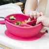 A close up of the pink Learning Bowl made from Silicone with food in it and a baby's hands bending the bowl.