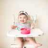 A giggling toddler girl sitting in her high chair with the pink Learning Bowl made from Silicone