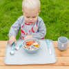 A young blond boy sitting outside looking at the food in the gray Learning Bowl made from Silicone
