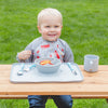 Cute blonde boy smiling and eating out of the gray Learning Bowl made from Silicone