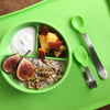 A Green Learning Spoon Set with yummy food inside the bowl sitting on green platemat.