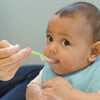A cute little infant looking up curiously while being fed with a Green Feeding Spoon.