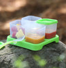Green food cubes holding baby food on a rock outside with a Green Feeding Spoon placed beside.