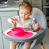A little girl sitting in her high chair using her pink Learning Cutlery Set to get food from her pink bowl