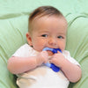 A little newborn boy laying on a green blanket and playing with the blue Everyday Teether made from Silicone in his mouth.