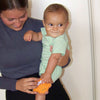 A young 6 month old boy mischievously smiling to someone while trying to grab at an orange owl Cool Calm Press that his mother is holding against his knee.