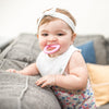 A cute infant girl playfully smiling and chewing one a pink first teether made from silicone while standing on a couch and pillows.
