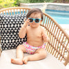 A young girl infant looking so fly in her Aqua Flexible Sunglasses while sitting in her wicker chair by the pool.