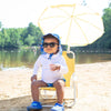 A young toddler looking like he was chilling in a beach chair with an umbrella while wearing black Flexible Sunglasses.