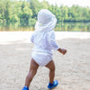 A little boy waddling away on the beach while wearing a white swim outfit including a white Flap Sun Protection Hat.