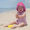 A cute happy little girl playing in the sand while being protected with her hot pink Flap Sun Protection Hat on.
