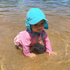 An adorable infant girl crawling through the water on the beach wearing a pink rashguard and an aqua Flap Sun Protection Hat.
