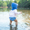 A little toddler boy waddling in the water while wearing the Royal Blue Flap Sun Protection Hat.