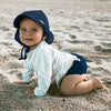 A cute toddler craddling along the beach while looking up and smiling and wearing a navy Flap Sun Protection Hat.