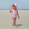 A young girl with a pink swim suit and the light pink pinstripe Bucket Sun Protection Hat walking on the beach waving toward someone behind her.