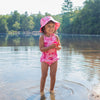 An adorable young girl standing in the shallow end of a lake holding a pink cup and wearing the pink hawaiian turtle Bucket Sun Protection Hat and a matching swimsuit.