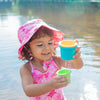 A young girl playing with toy water cups while wearing the pink hawaiian turtle Bucket Sun Protection Hat and a matching swimsuit.