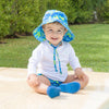 A lovable young boy sitting in the backyard smiling at the viewer while wearing Royal Blue Turtle Journey Bucket Sun Protection Hat.