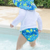 A young boy waddling in the shallow end of a pool while wearing Royal Blue Turtle Journey Bucket Sun Protection Hat and matching swim diaper.