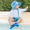 A young boy sitting on the edge of a pool in the backyard waving at someone out of view while wearing Royal Blue Turtle Journey Bucket Sun Protection Hat.